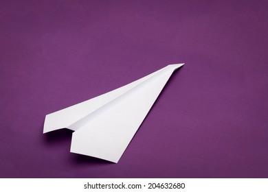 white paper plane on purple paper background