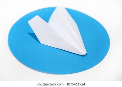 White paper plane on round blue circle. Abstract photo.