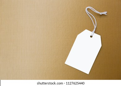 White paper price tag on shiny gold texture background, sale and advertise tag, business concept background