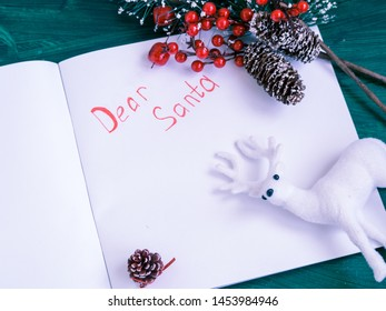 white paper sheet with dear santa note christmas deer and tree branches on green background