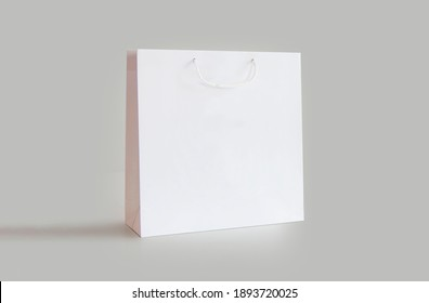 White paper shopping bag with handles isolated on light background