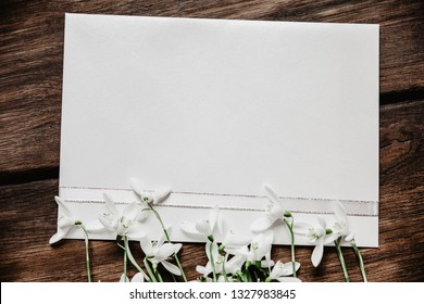 White paper with snowdrops on wooden background. Top view, copy space.