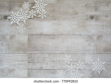 White paper snowflakes on wooden background with copy space, christmas and new year, minimalistic design