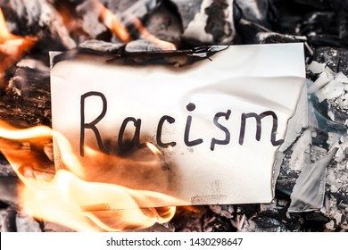 White paper with text of racism burning in fire. The concept of racism. Discrimination, racial problems
