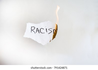 White paper with text racism burns. concept there is no racism