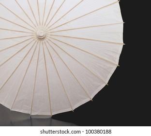 White paper umbrella with wood splines on black background