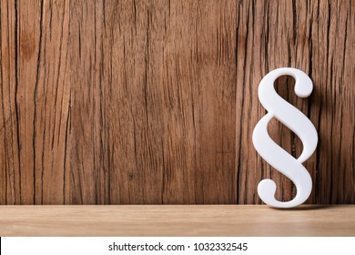 White Paragraph Symbol Leaning On Wooden Background