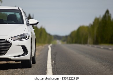 The white part of the car with a bumper and headlight on the background of an asphalt road and white road markings, close-up, front view