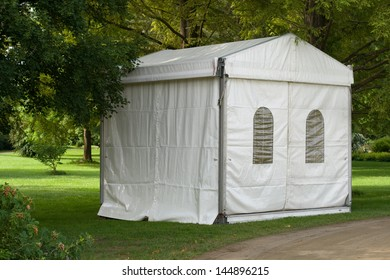 A white party or event tent on a meadow in a public park