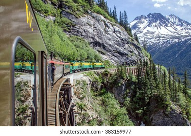 White Pass & Yukon Route Railroad travels along the cliffs heading towards Skagway, Alaska