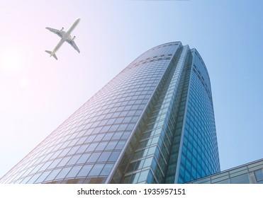 White passenger aircraft flies over a skyscraper