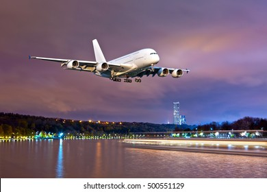 White passenger airplane in the colorful night sky. Aircraft flies over the river.