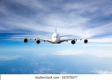 White passenger airplane flying high in the blue cloudy sky. Aircraft front view.