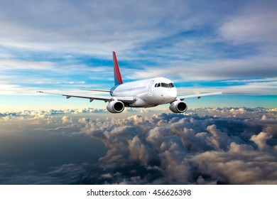 White passenger airplane with red and blue Tail. Aircraft is flying in the blue cloudy sunset sky.
