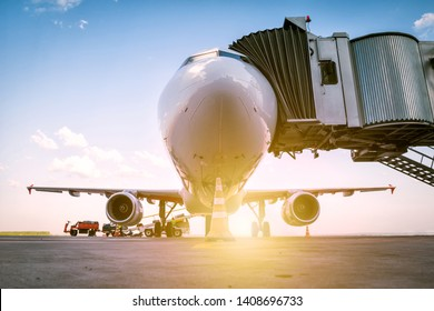 A white passenger airplane stands at the boarding bridge and is loaded with baggage in the rays of the morning sun