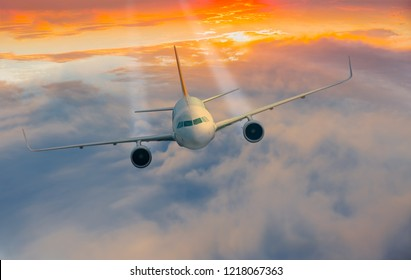White passenger airplane in the storm clouds at amazing sunset