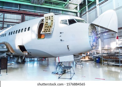 White passenger airplane under maintenance in the hangar. Checking mechanical systems for flight operations. The aircraft has opened weather radar