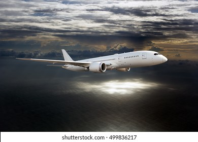 White passenger Dreamliner plane in the dark sky. Aircraft flies over the sea against the sunset clouds.
