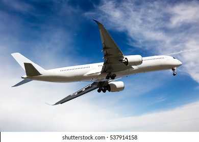 White passenger jet plane in the blue sky.  Aircraft flying high through the clouds.