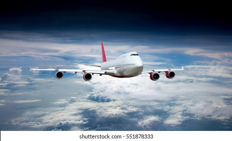 White passenger jet plane in the blue sky.  Aircraft flying high through the clouds. Airplane front view.
