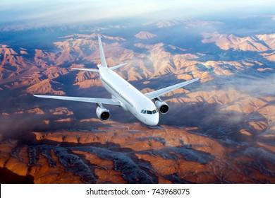 White passenger jet plane flies over the mountains