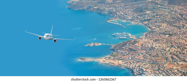 White passenger jet plane in the sky - Aircraft flies high over the city and and sea coast in the background Kusadasi  port and cruise ship - Kusadasi, Izmir
