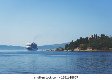 White passenger liner in the bay. Montenegro, Boka Kotorska bay on a hot summer day. Travel on a cruise liner to Montenegro.