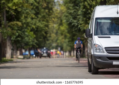 White passenger medium size commercial German luxury minibus van parked on city street with blurred silhouettes of pedestrians and moving car under green trees.