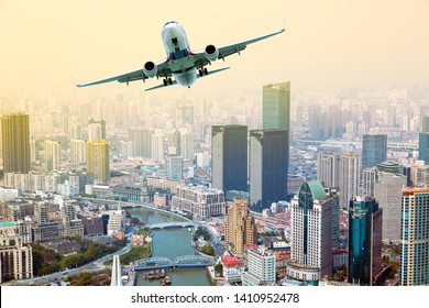 White passenger plane. Aircraft in flight. Aircraft fly over the skyscrapers of the big city. Front view of aircraft. Concept of travel and business.