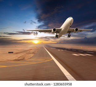 White passenger plane. Aircraft front view. Airplane take-off from airport runway during the sunset.