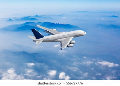 White passenger plane in the blue sky. Aircraft flies high over the clouds and foggy mountain landscape. Airplane side view.