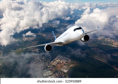 White passenger plane climbs through the clouds. Aircraft is flying high above the city.