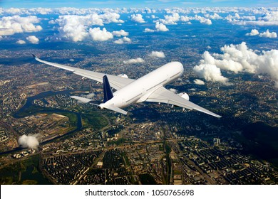 White passenger plane in flight. Aircraft  flies over the big city. Rear view of airplane.