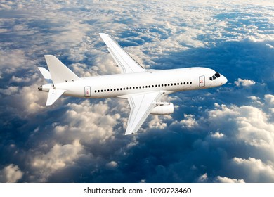 White passenger plane in flight. Aircraft fly high above the clouds. View from above.