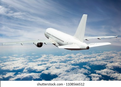 White passenger plane in flight. Aircraft fly away above the clouds. Back view of aircraft.