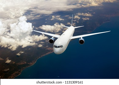 White passenger plane in flight. Aircraft fly high over the sea coast.