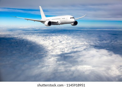 White passenger plane in flight. Aircraft  fly above the clouds.
