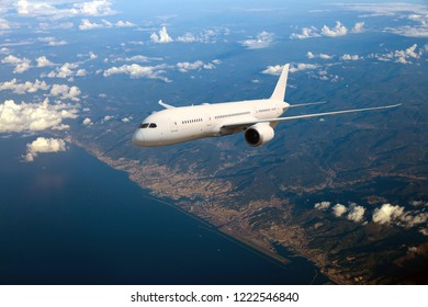 White passenger plane in flight. Aircraft fly high above the sea coast. Front view.
