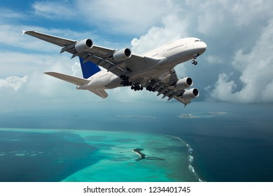White passenger plane in flight. Aircraft fly over the turquoise sea.