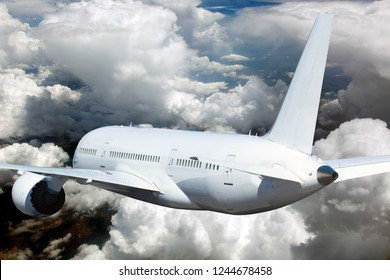 White passenger plane in flight. Aircraft flies high above the clouds. Rear view of aircraft. Close-up.