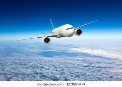 White passenger plane in flight. Aircraft flying high in the blue sky above the clouds.