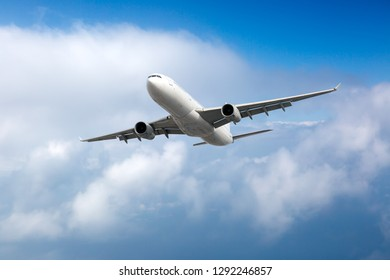 White passenger plane in flight. Aircraft flying high in the sky above the clouds.