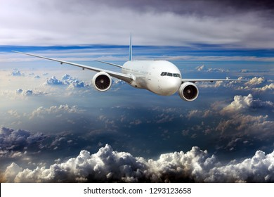 White passenger plane in flight. Aircraft flying high in the blue sky over the clouds.