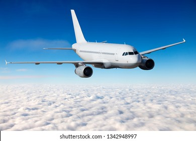White passenger plane in flight. Aircraft  fly above the clouds. Front view.