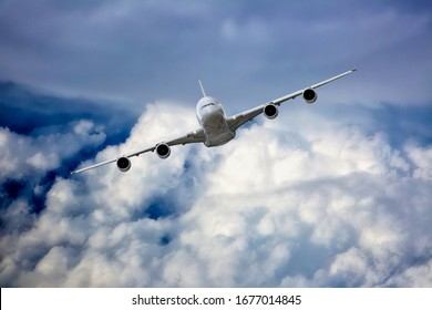 White passenger plane in flight. Aircraft  flies high over the clouds. Front view of aircraft. Left heeling.