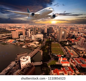White passenger plane in flight during the sunset. Aircraft  flies above the skyscrapers of the business center of the big city. Front view of aircraft.