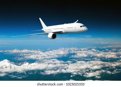 White passenger plane in flight. The plane flies high above a snow covered mountain landscape. Aircraft front view.