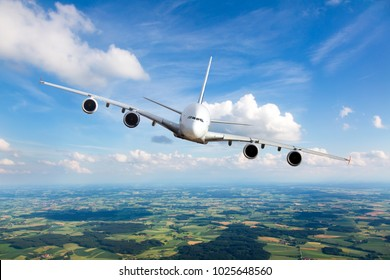 White passenger plane in flight. The plane flies against a background of a endless horizon. Aircraft right inclination / front view.