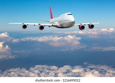 White passenger plane in flight. The plane flies against a background of a cloudy sky. Aircraft front view.