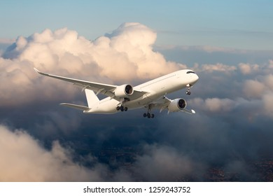White passenger plane in flight. The plane flies against a background of sunset clouds. Aircraft side view.